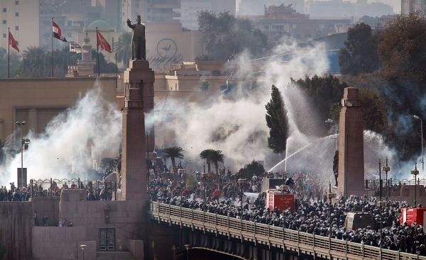 CAIRO, EGYPT - JANUARY 28: Riot police force protestors back across the Kasr Al Nile Bridge as they attempt to get into Tahrir Square on January 28, 2011 in downtown Cairo, Egypt. Thousands of police are on the streets of the capital and hundreds of arrests have been made in an attempt to quell anti-government demonstrations. (Photo by Peter Macdiarmid/Getty Images)