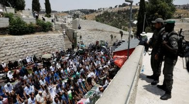 Israeli border police officers stand guard as Palestinians pray at Lions' Gate, the entrance to Jerusalem's Old City, in protest over Israel's new security measures at the compound housing al-Aqsa mosque